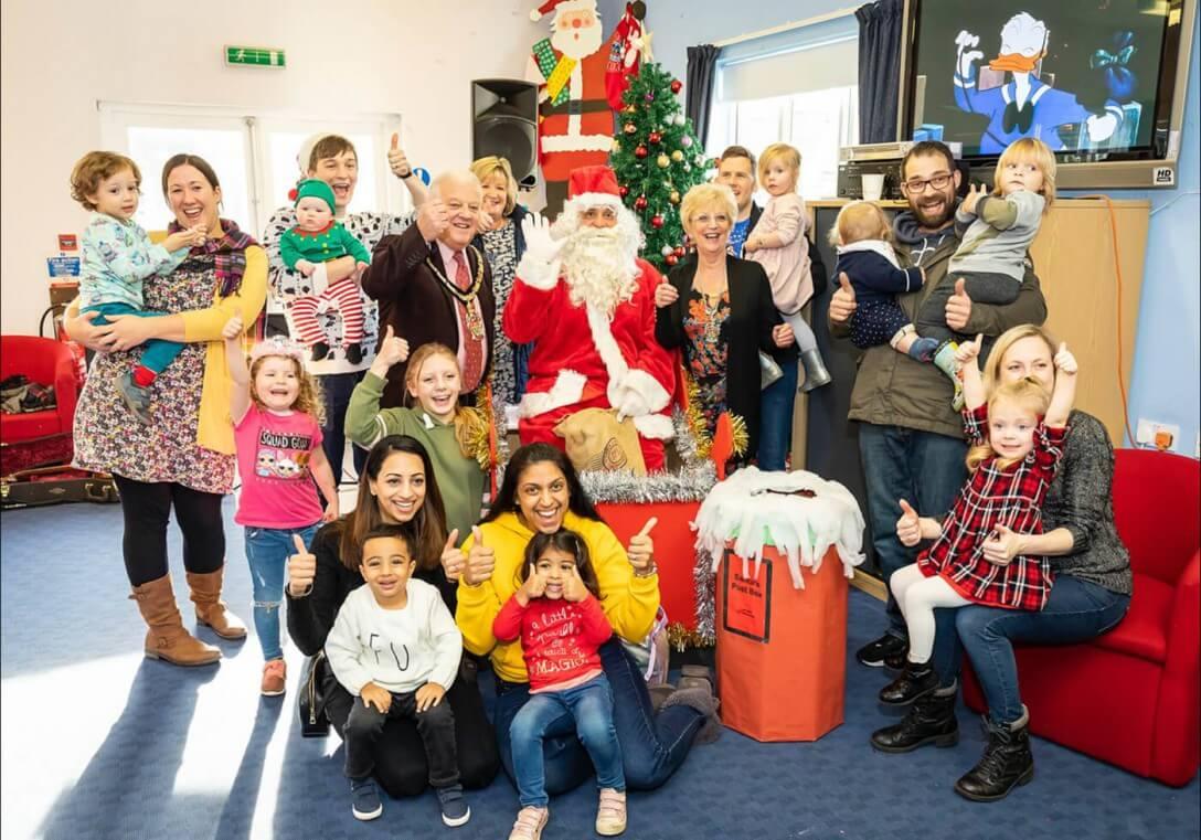 The community enjoying santa and his sack of gifts